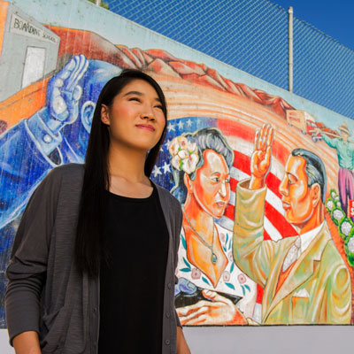 Immigrant woman stands in front of mural of man taking the U.S. citizenship oath.